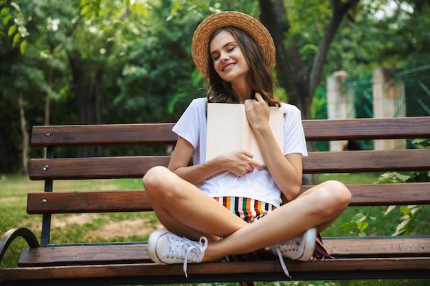 Felice giovane ragazza leggendo un libro mentre era seduto al parco all'aperto