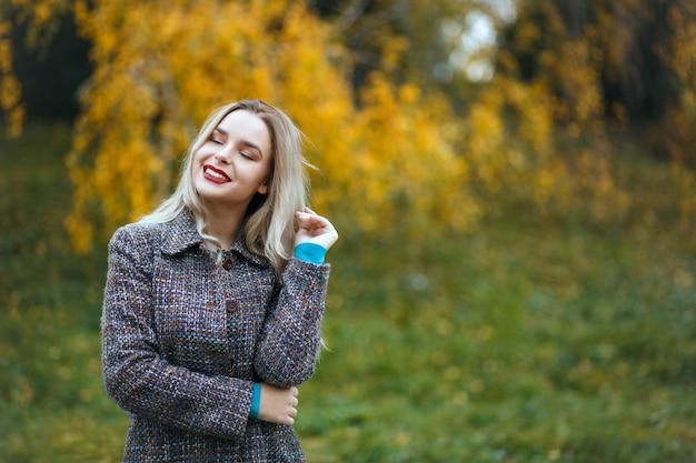 Deliziosa donna bionda con labbra rosse che indossa un cappotto elegante godendosi il tempo nella foresta autunnale. spazio vuoto
