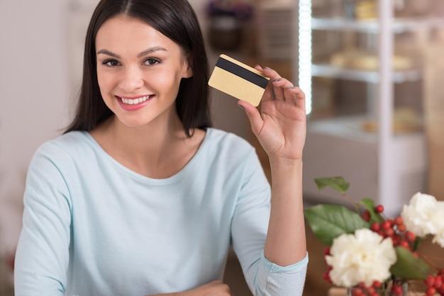 Deliziosi sconti. bella giovane donna allegra sorridente e mostrando una carta sconto mentre ci si rilassa in un caffè.