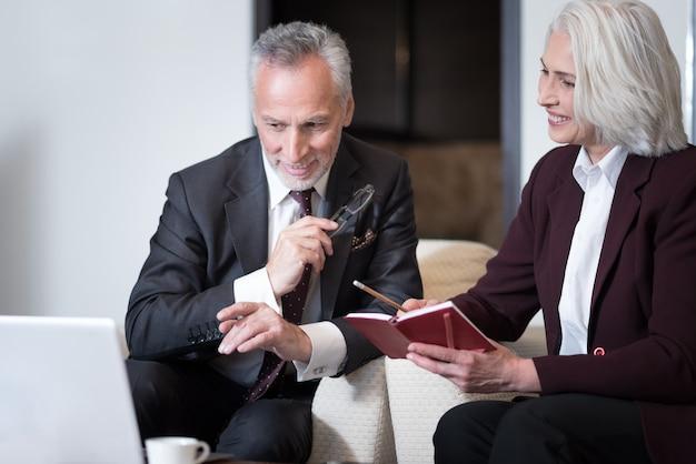 Delizioso dal processo. felice imprenditore invecchiato felice sorridente e seduto in ufficio davanti al computer portatile mentre si lavora con il suo collega e la condivisione di idee