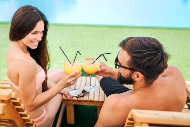 La coppia deliziosa e positiva è seduta sui lettini e si guarda l'un l'altro. loro sorridono. la coppia ha bicchieri di cocktail. lo toccano.