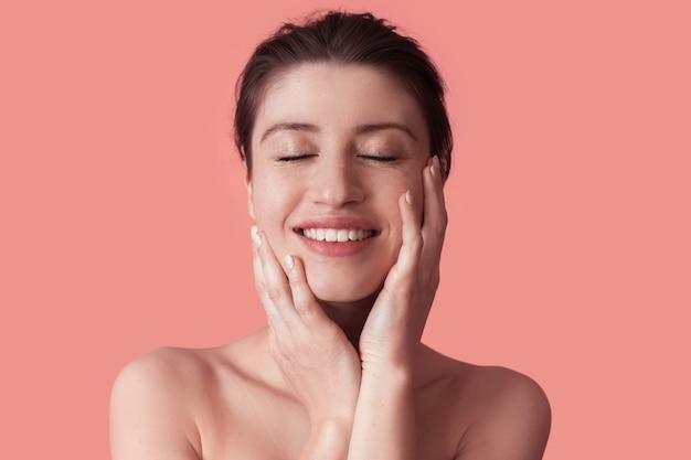 Deliziosa donna con le lentiggini in posa con le spalle svestite su una parete rosa dello studio sorride toccando con le palme il viso