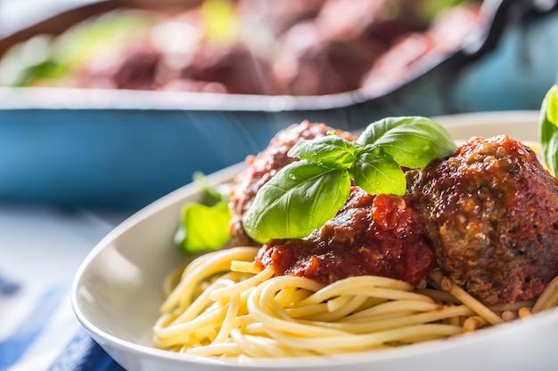 Polpette di carne di manzo del pasto italiano delizioso con spaghetti di pasta e basilico in piatto bianco.
