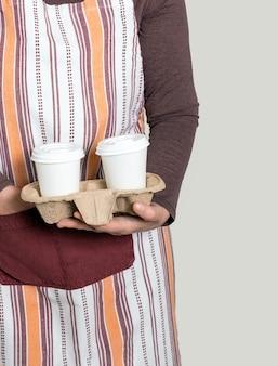 Consegnare o barista tenendo il contenitore da asporto con due tazze di caffè bianche.