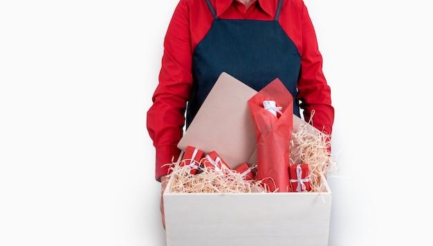 Consegnare detiene regali, sacchetto di imballaggio e bottiglia di vino