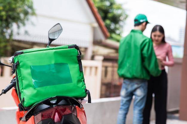 Consegnare la motocicletta con una custodia verde per alimenti isotermici davanti all'appartamento o al condominio con il corriere e il cliente sfocati. esprimere la consegna degli ordini di cibo presso l'edificio per uffici tramite app. nuovo normale.