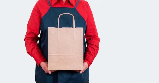 Consegnare le mani in camicia rossa tenere la borsa da imballaggio