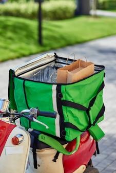 Consegnare cibo dal ristorante a casa tua zaino termico verde con sacchetto di carta su scooter