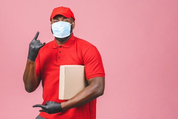 L'impiegato dell'uomo afroamericano di consegna nei guanti della maschera di protezione della maglietta in bianco del berretto rosso tiene la scatola di cartone vuota