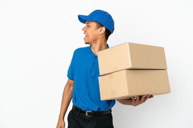 Consegna uomo afroamericano isolato su sfondo bianco ridendo in posizione laterale