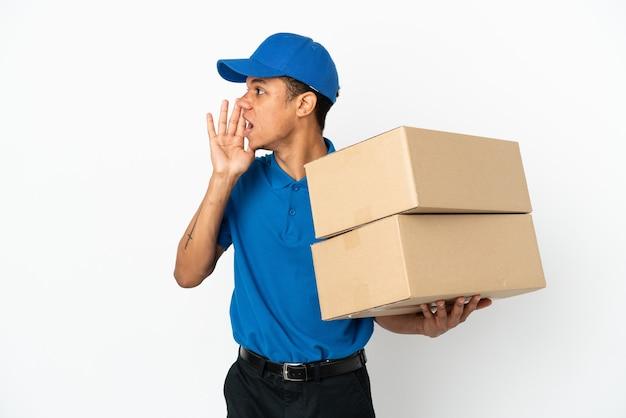 Uomo afroamericano di consegna isolato su fondo bianco che grida con la bocca spalancata al lato