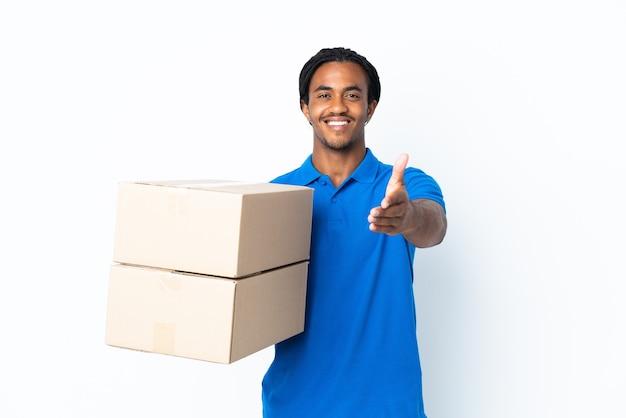 Consegna uomo afroamericano con trecce isolato su sfondo bianco stringe la mano per chiudere un buon affare