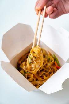 Consegna di noodles asiatici con verdure in una scatola bianca e bastoncini di sushi