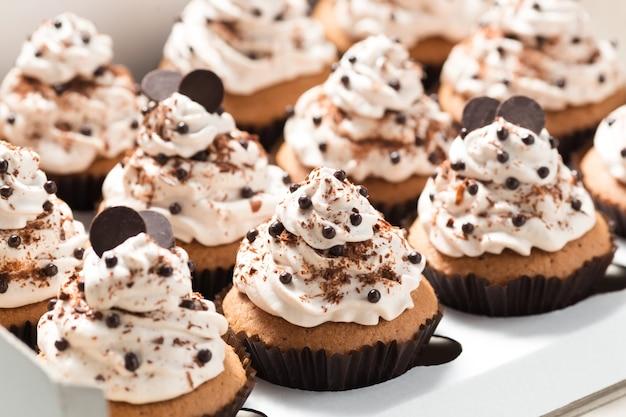 Scatola di consegna con cupcakes al caffè decorati con crema al burro moka e gocce di cioccolato