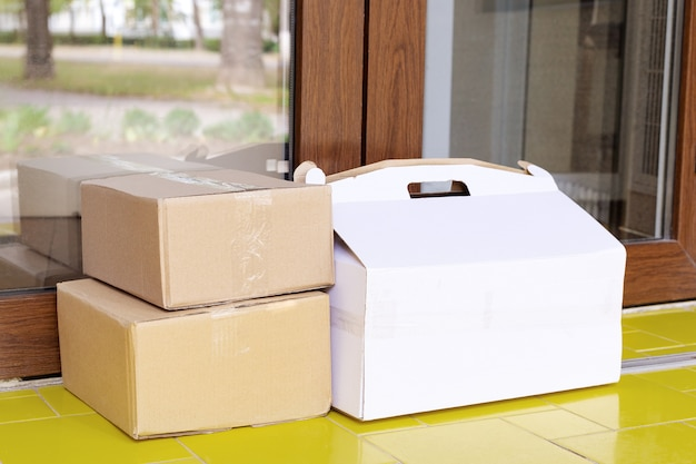 Scatole di consegna a domicilio a casa. consegna di cibo senza contatto. acquisti sicuri l'e-commerce acquista pacchi a casa. scatole consegnate a domicilio tramite corriere, postino.