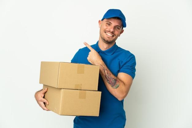 Consegna uomo caucasico isolato sul muro bianco che punta di lato per presentare un prodotto