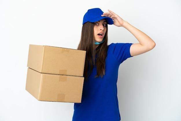Consegna donna caucasica isolata su sfondo bianco facendo un gesto a sorpresa mentre guarda di lato