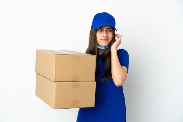 Consegna donna caucasica isolata su sfondo bianco frustrata e che copre le orecchie