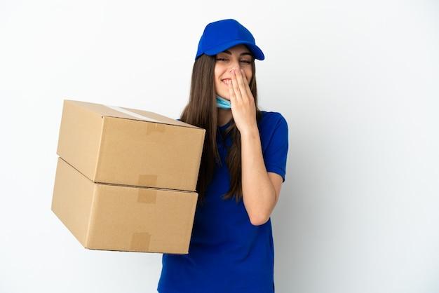 Consegna donna caucasica isolata su sfondo bianco felice e sorridente che copre la bocca con la mano