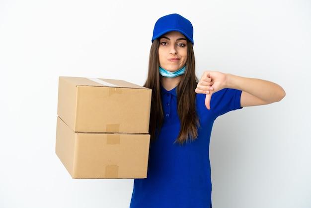 Consegna donna caucasica isolata su sfondo bianco che mostra il pollice verso il basso con espressione negativa
