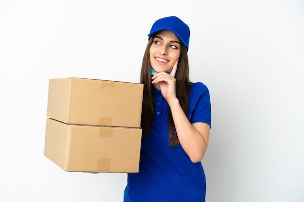 Consegna donna caucasica isolata su sfondo bianco pensando a un'idea mentre guarda in alto