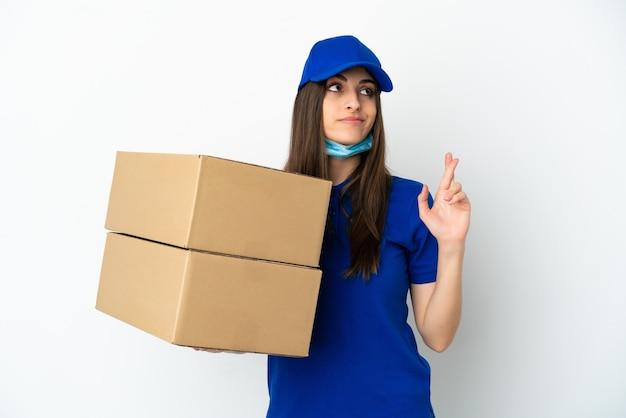 Consegna donna caucasica isolata su sfondo bianco con le dita incrociate e augurando il meglio