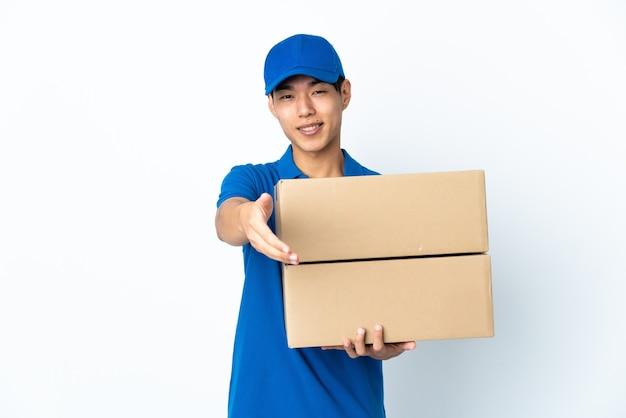 Uomo cinese di consegna isolato sul muro bianco che stringe la mano per chiudere un buon affare
