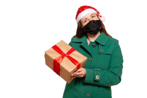 Consegna di un regalo di natale a casa con mascherina medica. consegna del regalo per il natale isolato su bianco