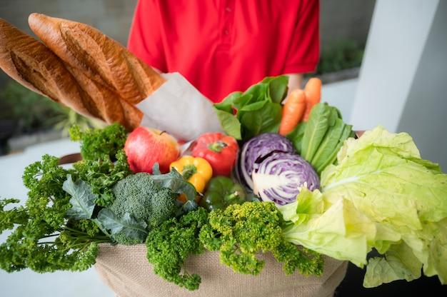 Lavoratore della società di consegna che tiene il sacchetto della spesa, ordine del cibo, servizio di supermercato, accettazione della scatola della spesa dalla donna delle consegne a casa, consegna di verdure biologiche fresche