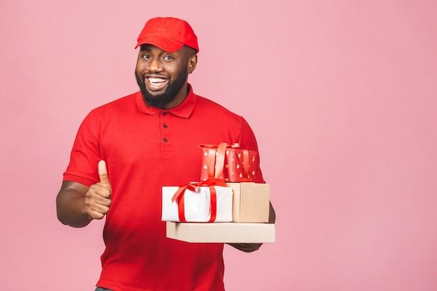 Concetto di consegna. uomo nero di consegna afroamericano che trasporta pacchi e scatole regalo. pollice su.