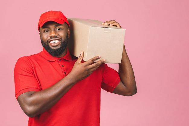 Concetto di consegna. african american consegna uomo nero che trasportano pacchi isolate su sfondo rosa.