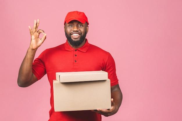 Concetto di consegna. uomo nero di consegna afroamericano che trasporta il pacco. ok segno.