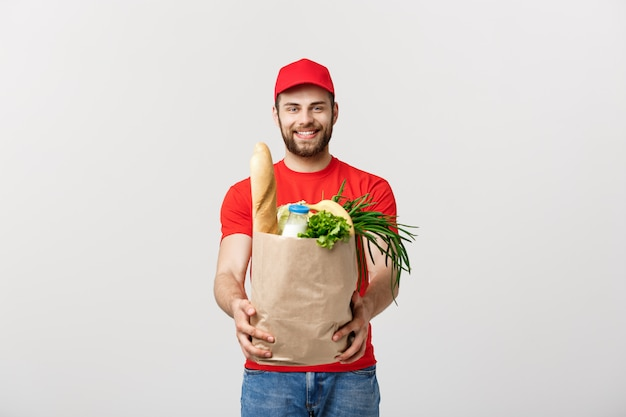 Concetto di consegna - uomo di consegna bello cacasiano che trasporta il sacchetto del pacchetto di alimentari