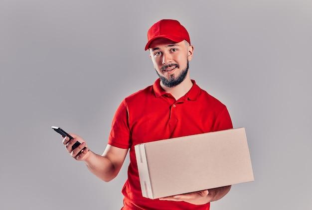 Concetto di consegna - ritratto di un bell'uomo di consegna caucasico o corriere con scatola che mostra il telefono cellulare per controllare l'ordine. isolato su sfondo grigio studio. copia spazio.