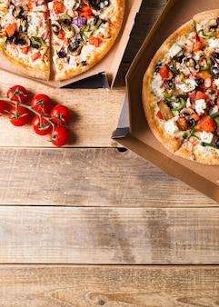 Concetto di consegna. pizza vegetale in scatola di cartone aperta sul tavolo di legno, copia spazio, verticale