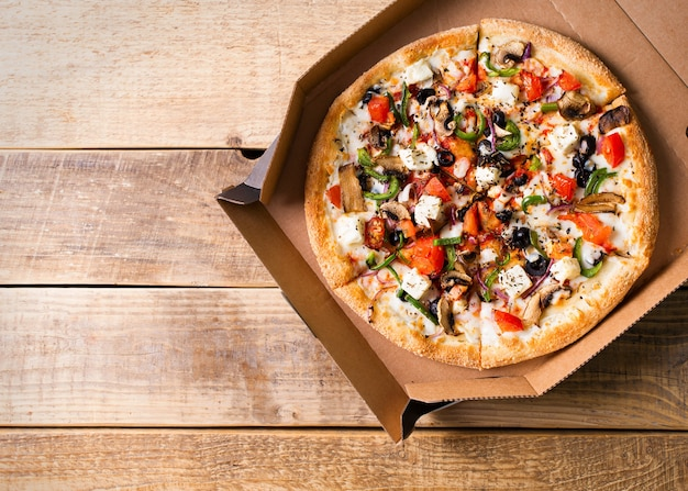 Concetto di consegna. pizza vegetale in scatola di cartone aperta sul tavolo di legno, copia dello spazio