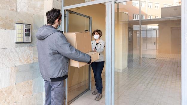 Il corriere consegna consegna il pacco alla donna alla sua porta