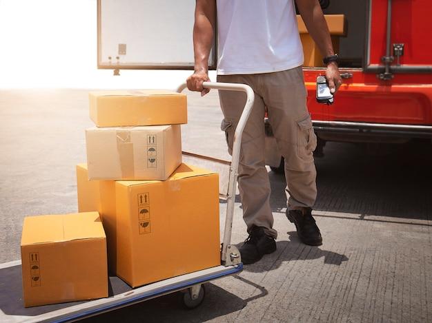 Corriere di consegna che guida il carrello con scatole per pacchi per l'invio a una scatola di spedizione per furgone per la consegna del cliente