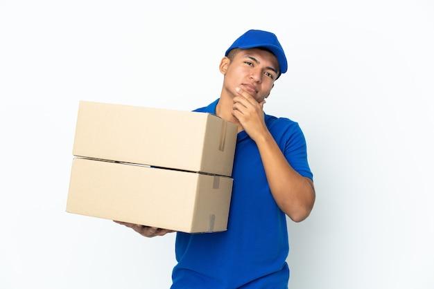 Uomo ecuadoriano di consegna isolato sulla parete bianca che osserva in su mentre sorride