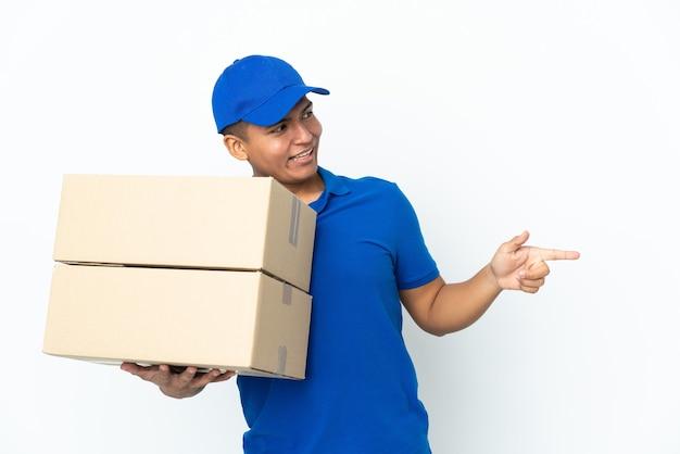 Consegna uomo ecuadoriano isolato sul muro bianco che punta il dito di lato e presenta un prodotto