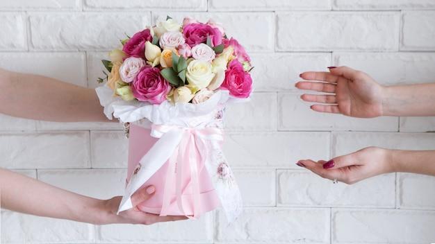 Consegna di un laboratorio floreale. il cliente riceve il suo ordine: un mazzo di rose rosa e giallo pallido. il corriere a mano passa i fiori all'acquirente