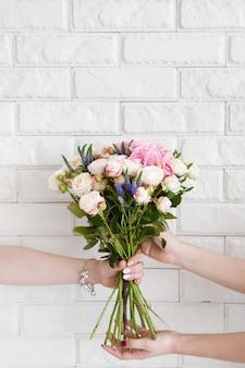 Consegna di un laboratorio floreale. il cliente riceve il suo ordine: un mazzo di rose rosa e fiori di campo. il corriere a mano passa i fiori all'acquirente