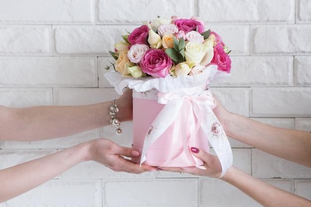 Consegna di un laboratorio di floristica. il cliente riceve il suo ordine: un mazzo di rose rosa e giallo pallido. il corriere a mano passa i fiori all'acquirente. concetto di piccola impresa