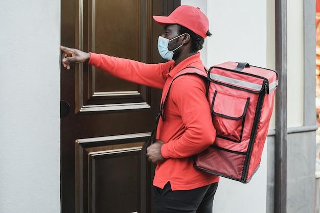 Uomo di consegna cibo con borsa termica che suona il campanello mentre indossa la maschera di sicurezza