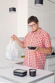 Cibo a domicilio, prodotti a domicilio. shopping e concetto di cibo sano. giovane in camicia a quadri rossa che tiene in mano un sacchetto di plastica usa e getta con consegna di cibo nella cucina moderna