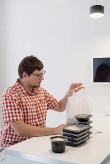 Cibo a domicilio, prodotti a domicilio. shopping e concetto di cibo sano. giovane uomo in camicia a quadri rossa giovane uomo che smista scatole per la consegna di cibo nella cucina moderna nella cucina moderna Foto Premium