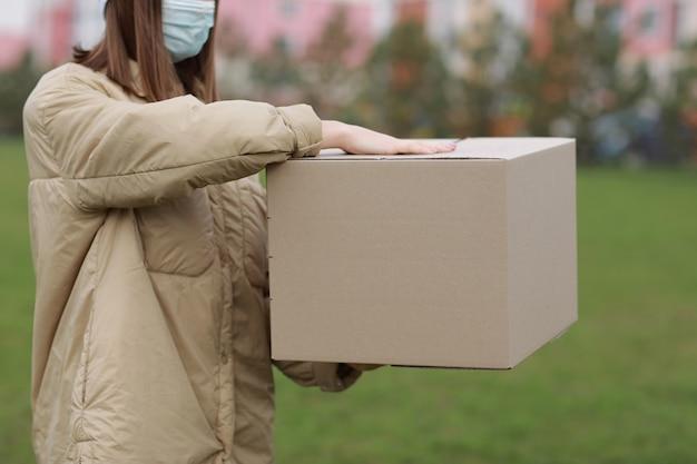 Ragazza delle consegne in maschera medica viso tenere la scatola di cartone vuota all'aperto su uno sfondo di complesso residenziale