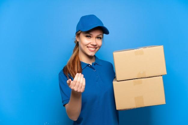 Ragazza di consegna sopra la parete blu isolata che invita a venire con la mano. felice che tu sia venuto
