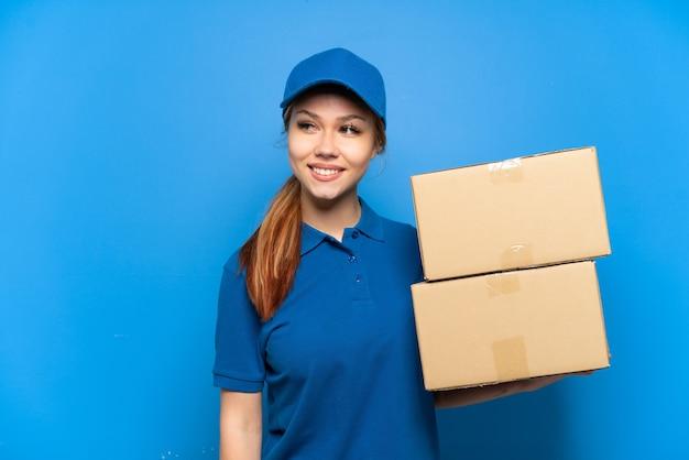 Ragazza delle consegne sopra il muro blu isolato che guarda di lato e sorride