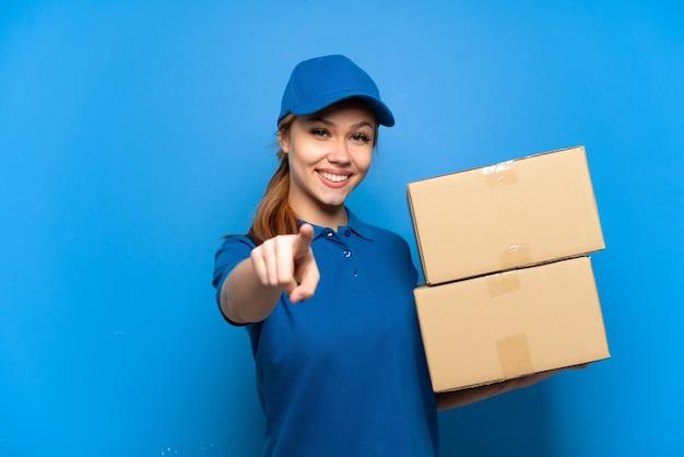 Ragazza di consegna sopra la parete blu isolata che indica la parte anteriore con l'espressione felice